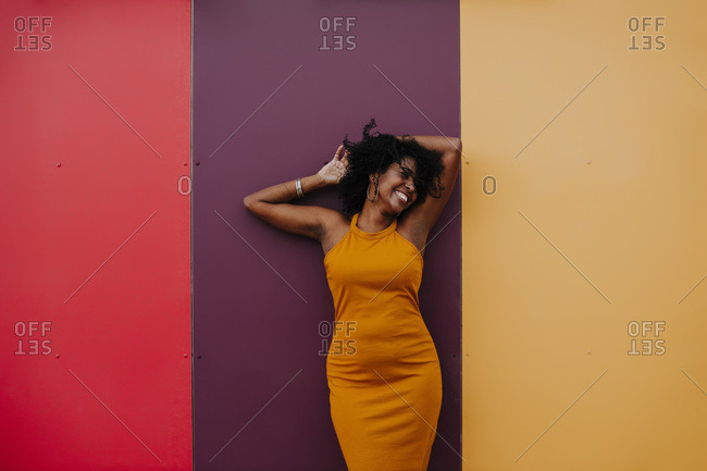 Carefree woman with hand in hair standing against colorful wall