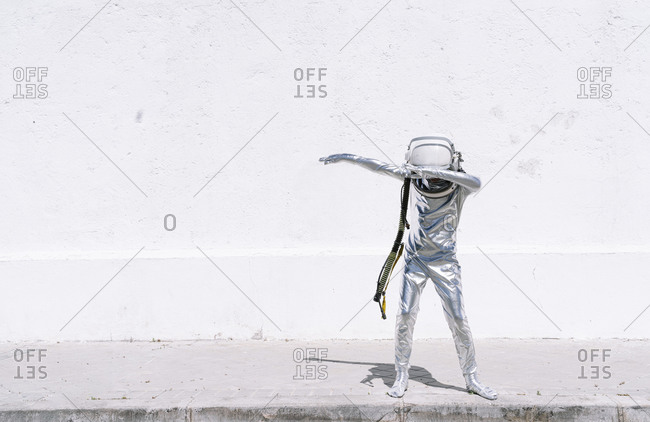 Boy in astronaut costume dabbing movement while standing against wall