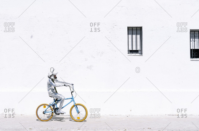 Playful boy in astronaut cycling bicycle against wall