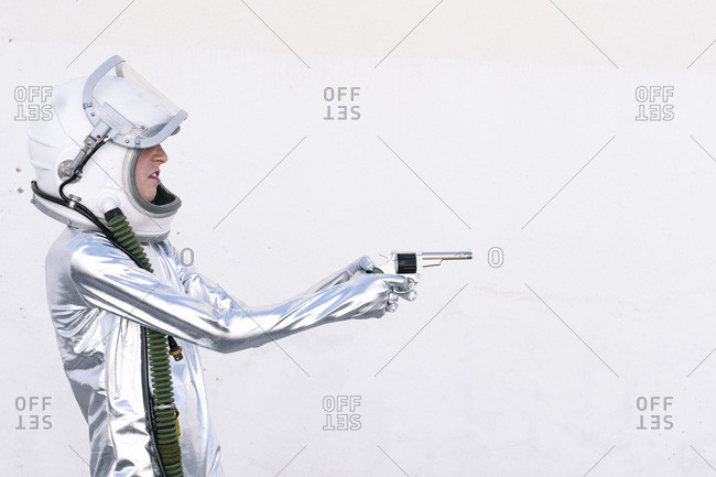Boy wearing astronaut playing with toy gun while standing against wall