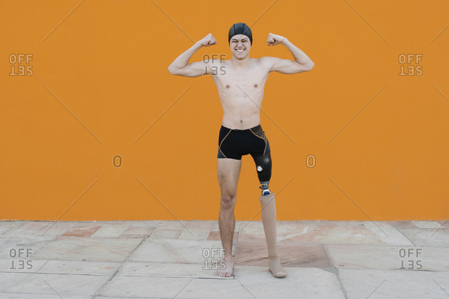 Young man flexing muscles standing against wall