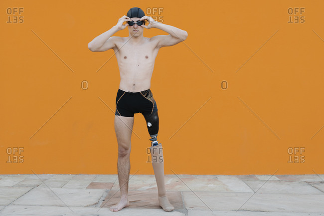 Disabled young man wearing swimming goggles while standing against orange wall