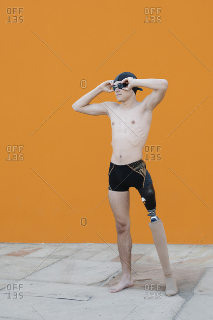 Amputee male wearing swimming goggles standing against wall