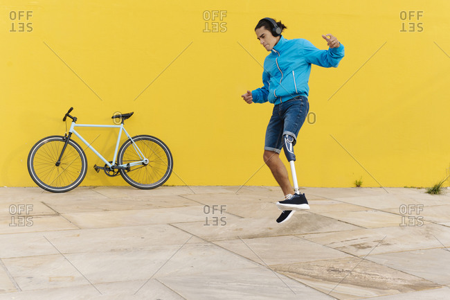 Disabled man with headphones listening music while dancing against yellow wall