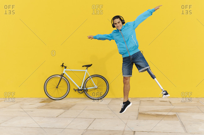 Smiling man with headphones jumping with arms outstretched against yellow wall