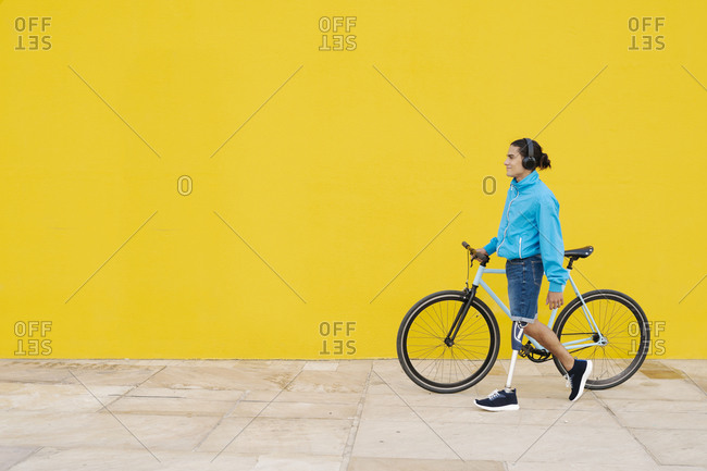 Man with artificial limb and foot walking with bicycle against yellow wall