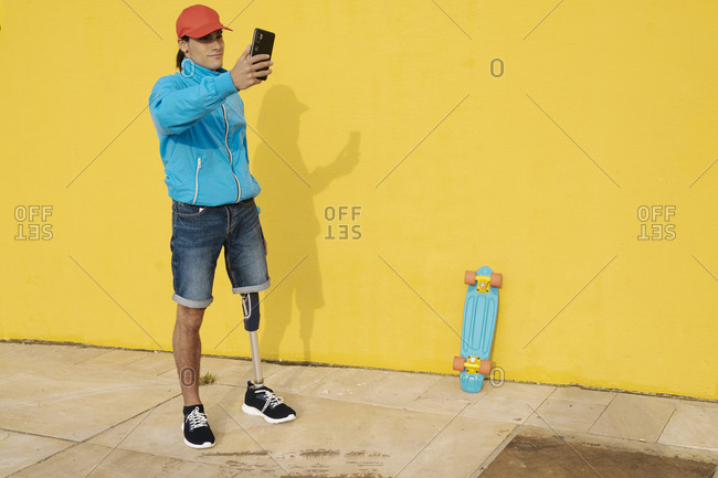 Man wearing cap taking selfie while standing by yellow wall