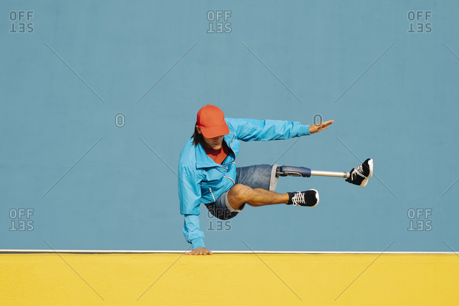 Young disabled man doing handstand against multi colored wall