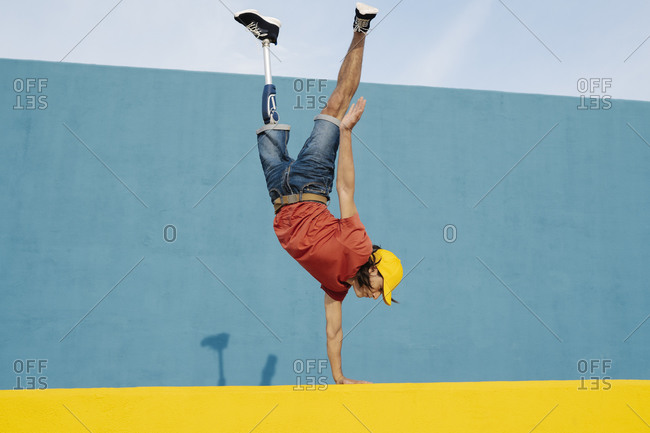 Young man with artificial limb and foot doing handstand against multi colored wall