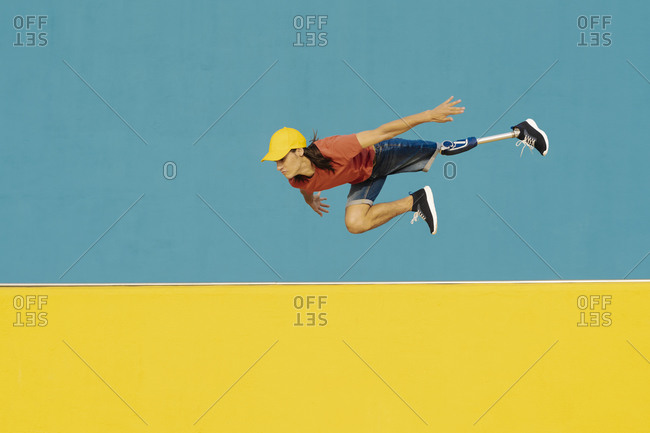 Athlete with artificial limb and foot jumping against multi colored wall