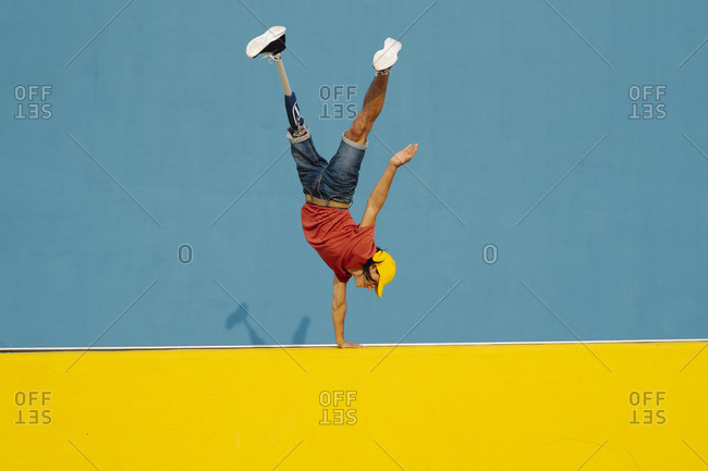 Man practicing handstand on multi colored wall