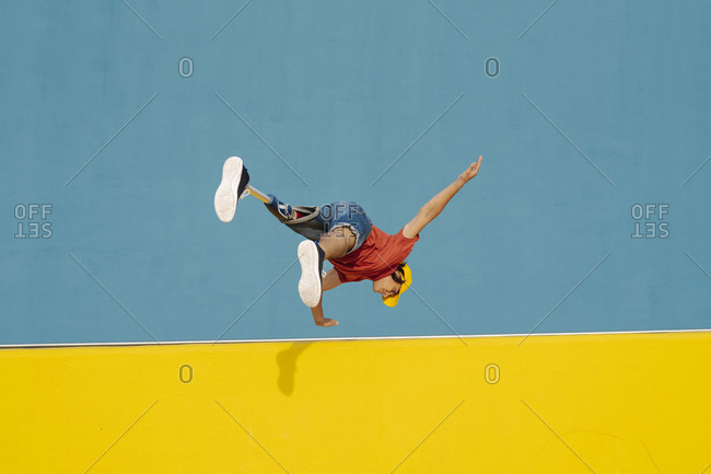 Athlete practicing handstand while jumping against multi colored wall