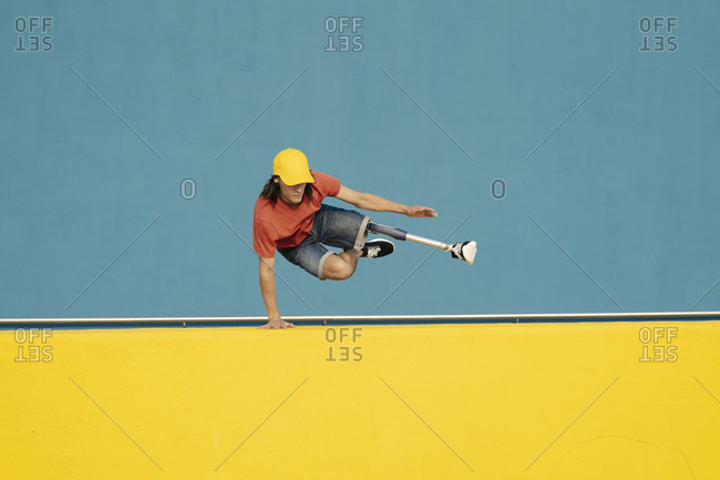 Disabled athlete doing handstand against multi colored wall