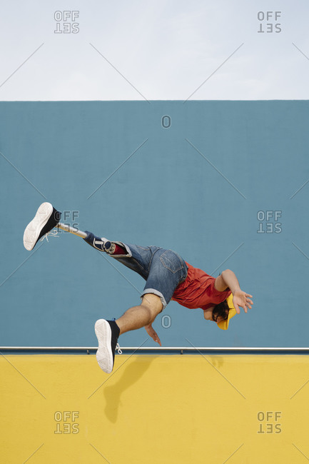 Athlete jumping against multi colored wall