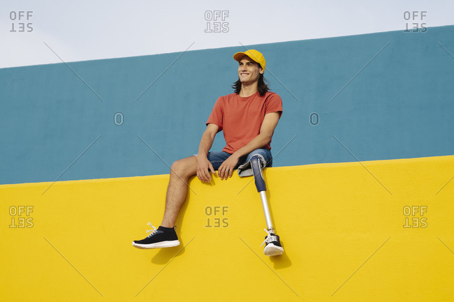 Smiling young man sitting against on multi colored wall