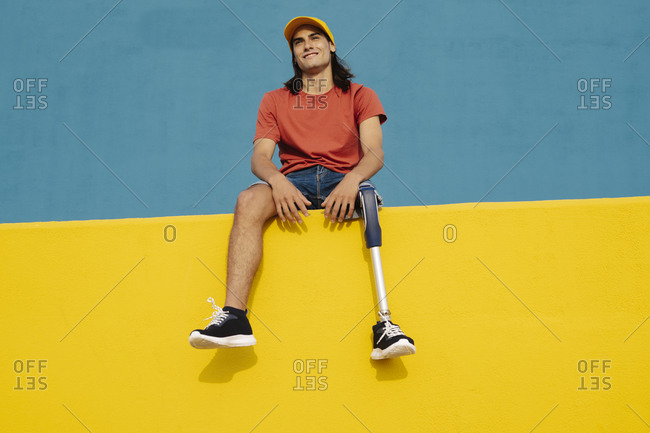 Athlete smiling while sitting on multi colored wall