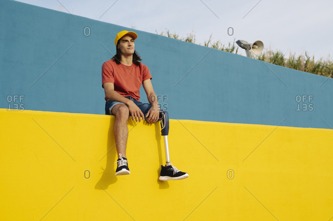 Disabled man wearing cap sitting on multi colored wall