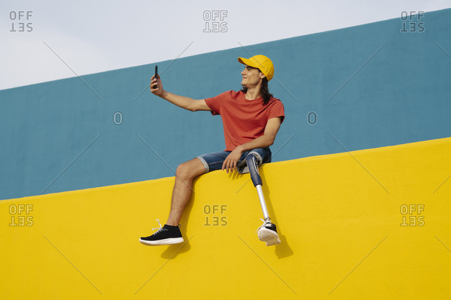 Smiling man taking selfie while sitting on multi colored wall