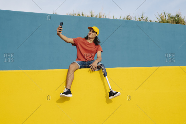 Young man taking selfie while sitting on multi colored wall