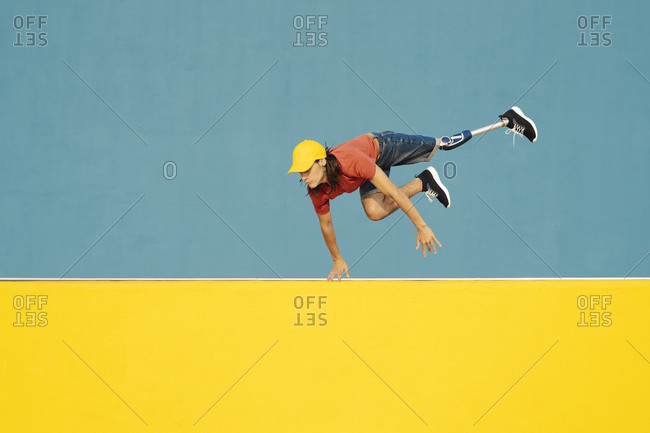 Man with physical disability jumping against multi colored wall