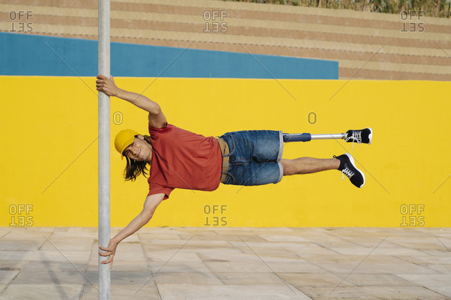 Athlete holding pole while balancing body weight against multi colored wall