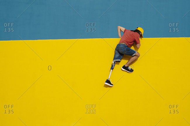 Disabled athlete putting efforts to climb multi colored wall