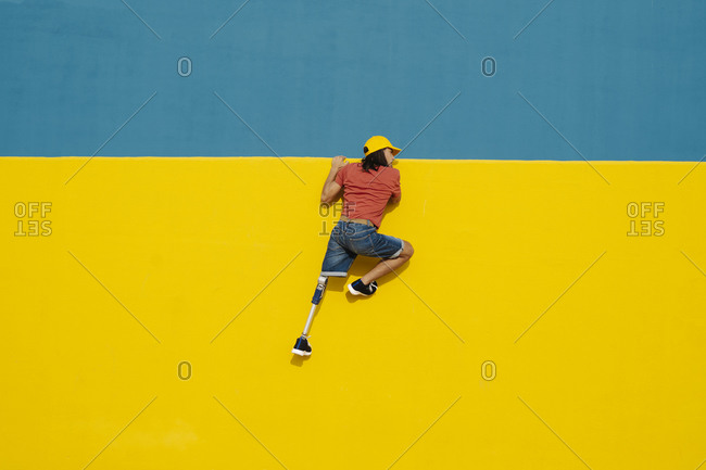 Young man putting efforts to climb multi colored wall