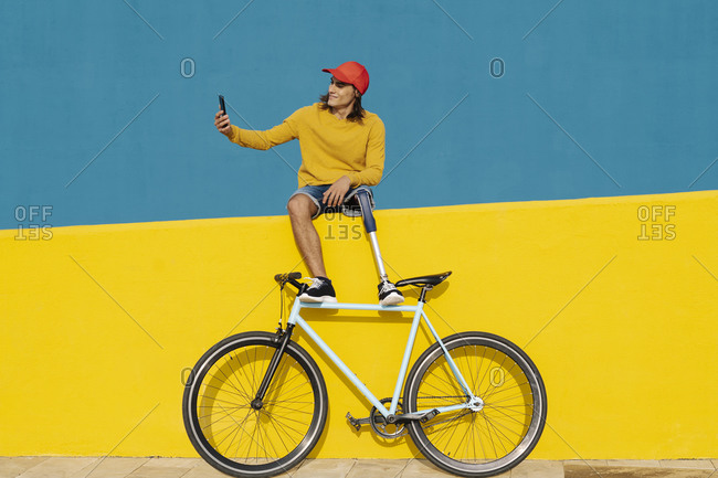 Man taking selfie while sitting on multi colored wall over bicycle