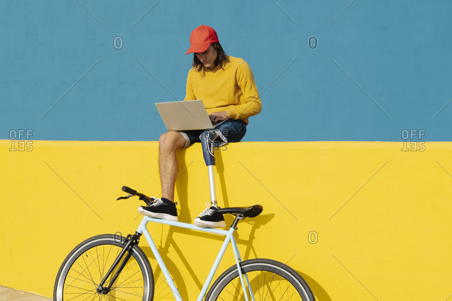 Man with artificial limb and foot working on laptop while sitting on multi colored wall