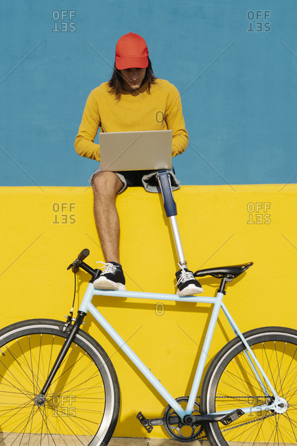 Young man with bicycle working on laptop while sitting on multi colored wall
