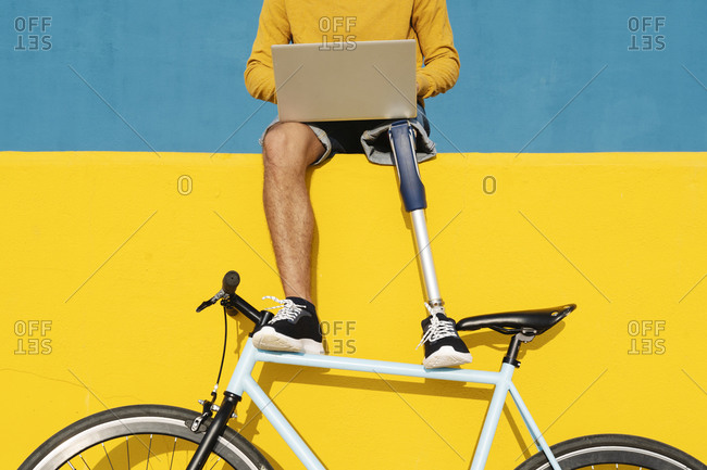 Man with artificial limb and foot using laptop while sitting on multi colored wall