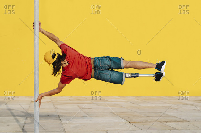 Young athlete holding pole while balancing body weight against multi colored wall