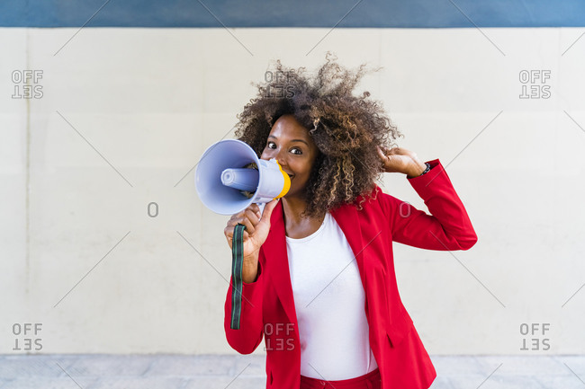 Mid adult woman using megaphone while standing against wall