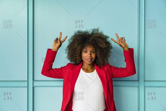 Mid adult woman gesturing while standing against blue wall
