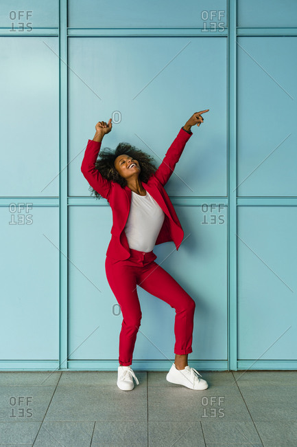 Mid adult woman cheerfully dancing against wall