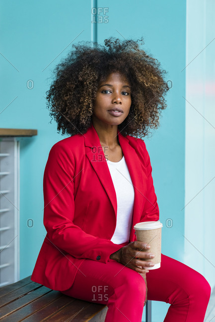 Woman with disposable coffee cup sitting on bench