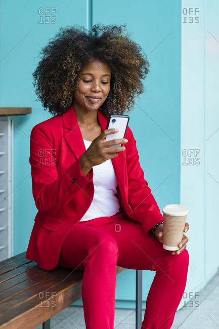 Woman holding disposable coffee cup while using smart phone sitting on bench