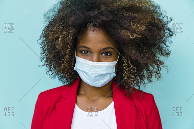 Woman wearing protective face mask standing against wall
