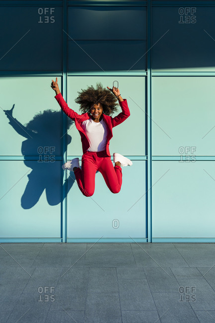 Cheerful woman with hand raised jumping against wall