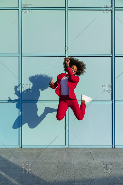 Woman enjoying while jumping against wall