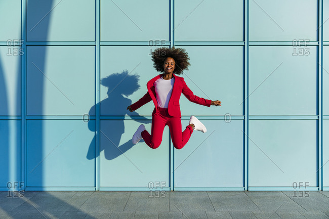 Smiling woman jumping against blue wall on sunny day