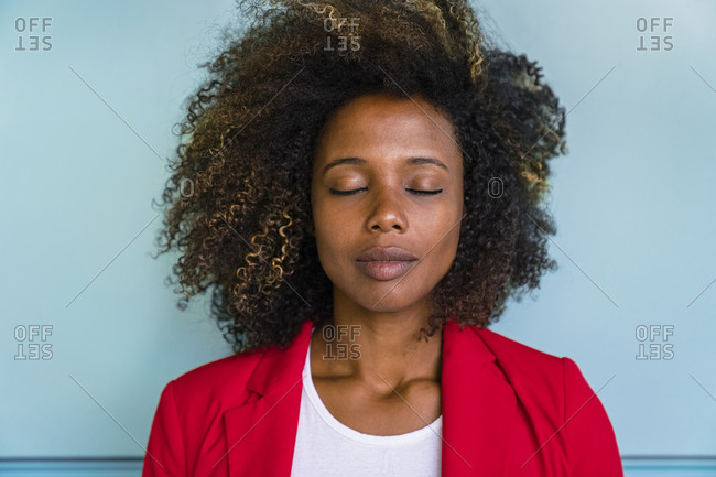 Thoughtful woman with closed eyes standing against wall