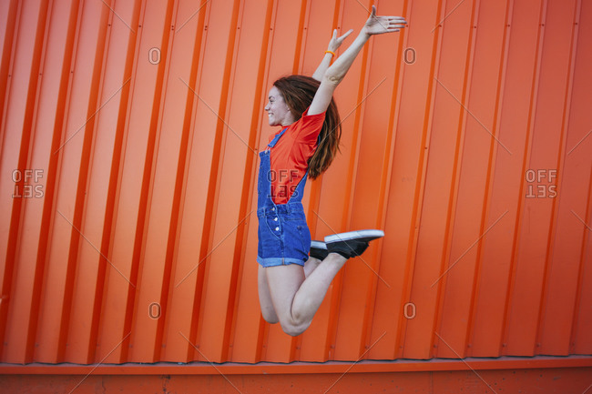 Smiling woman with hand raised jumping against orange wall