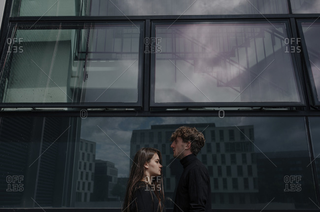 Young couple with face to face standing by building in city