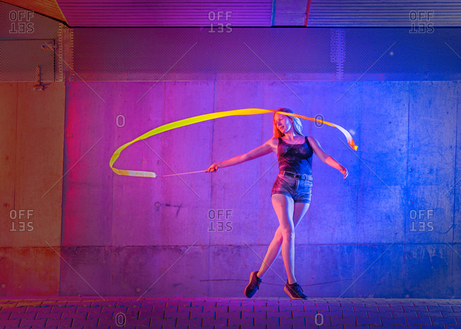 Woman spinning ribbon while dancing against wall