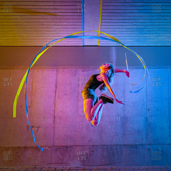 Woman jumping while spinning ribbon against wall