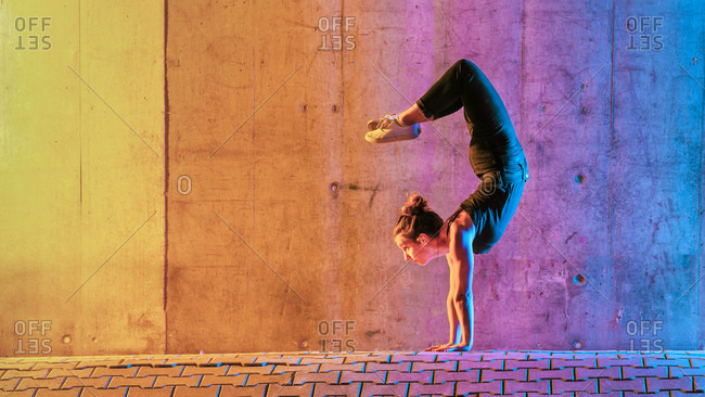 Woman practicing gymnastic in multi colored light against wall