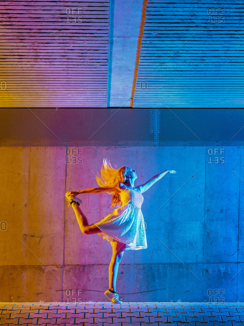 Woman dancing in multicolored light against wall