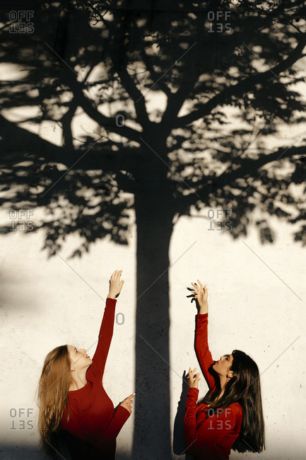 Young women with hands raised by shadow on wall
