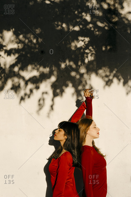 Young friends with hands raised standing back to back by shadow on wall